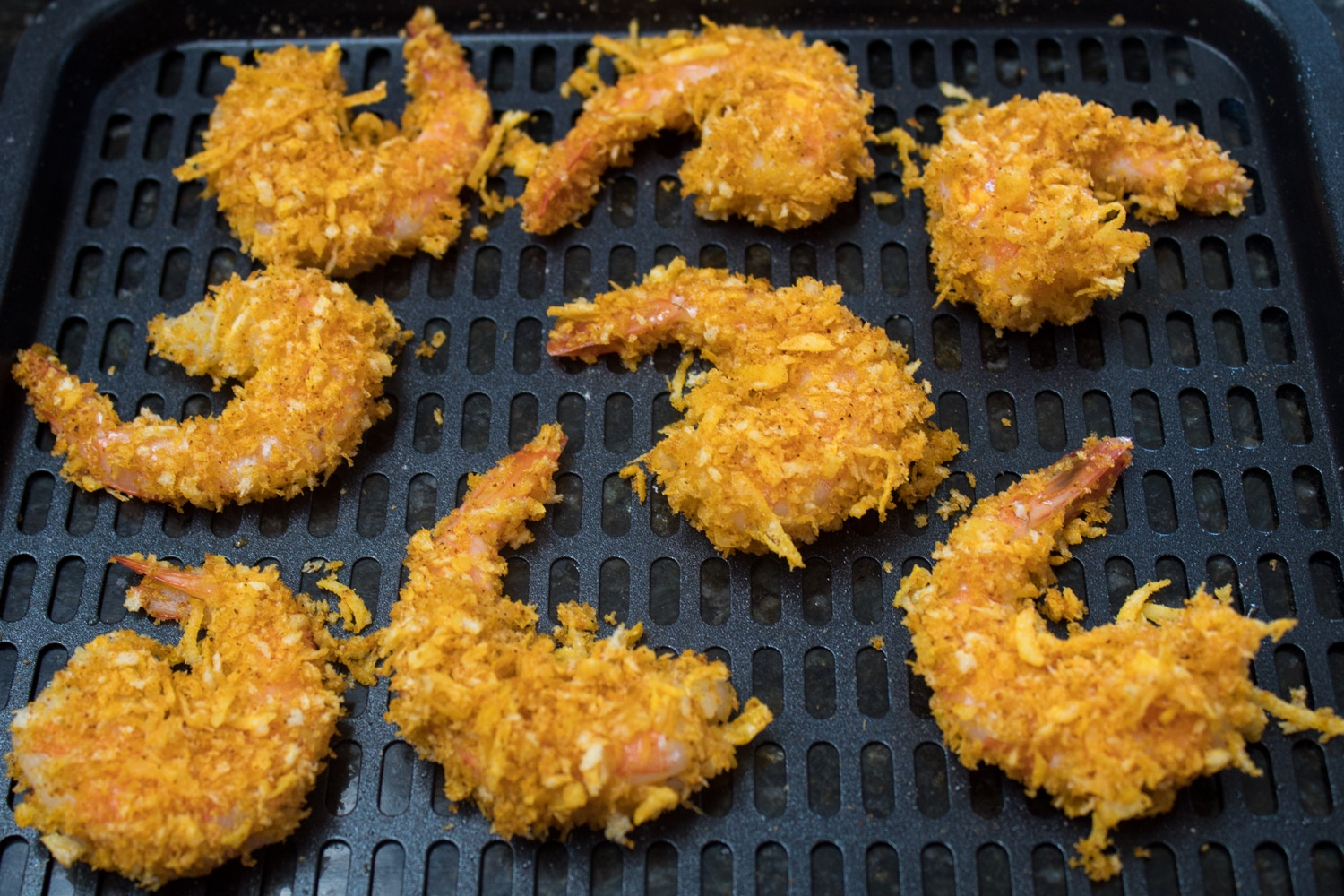 Coconut breading coated shrimp on the air fryer rack ready to go into the preheated instant pot vortex plus air fryer model.