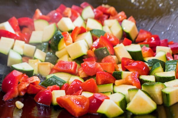 kung pao chicken vegetables (zucchini and red bell peppers) being stir fried in wok
