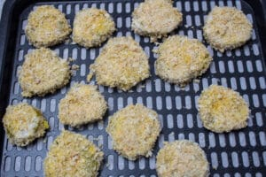 panko breaded pickle chips spaced apart on the non stick spray coated air fryer tray
