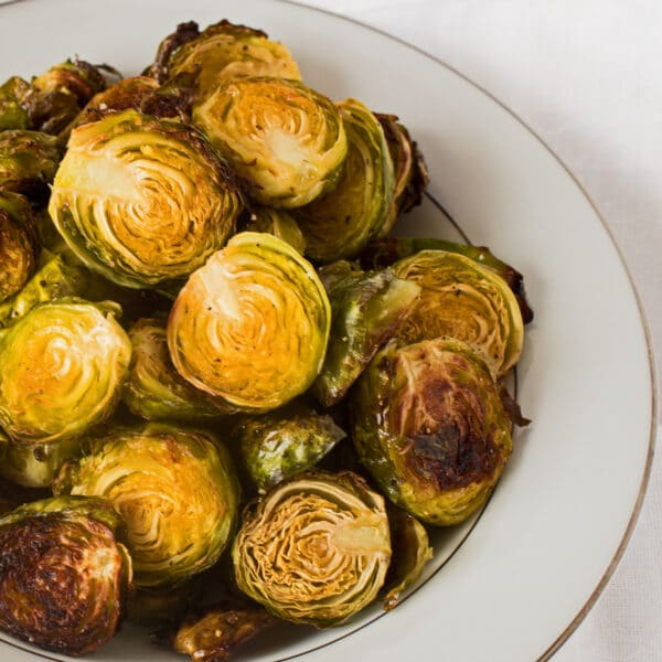 roasted brussel sprouts showing golden caramelized color in a white serving bowl on white background