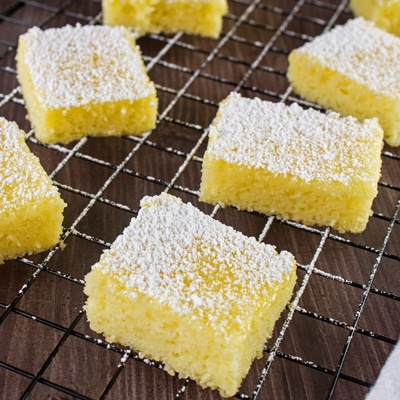 small square image of easy two ingredient lemon bars cut and dusted with powdered sugar, set on a black wire cooling rack over wood grain surface