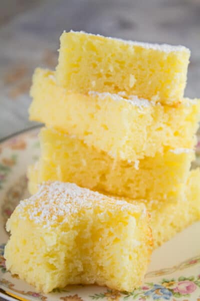 tall vertical image showing 2 ingredient lemon bars stacked four high on a light floral plate with gold trim