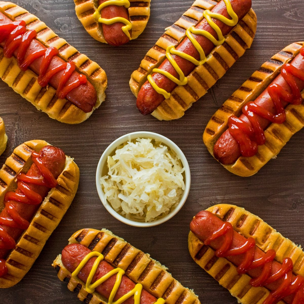 Overhead square image at top showing air fryer hot dogs in buns with ketchup and mustard on brown background with a white bowl of sauerkraut near the center.