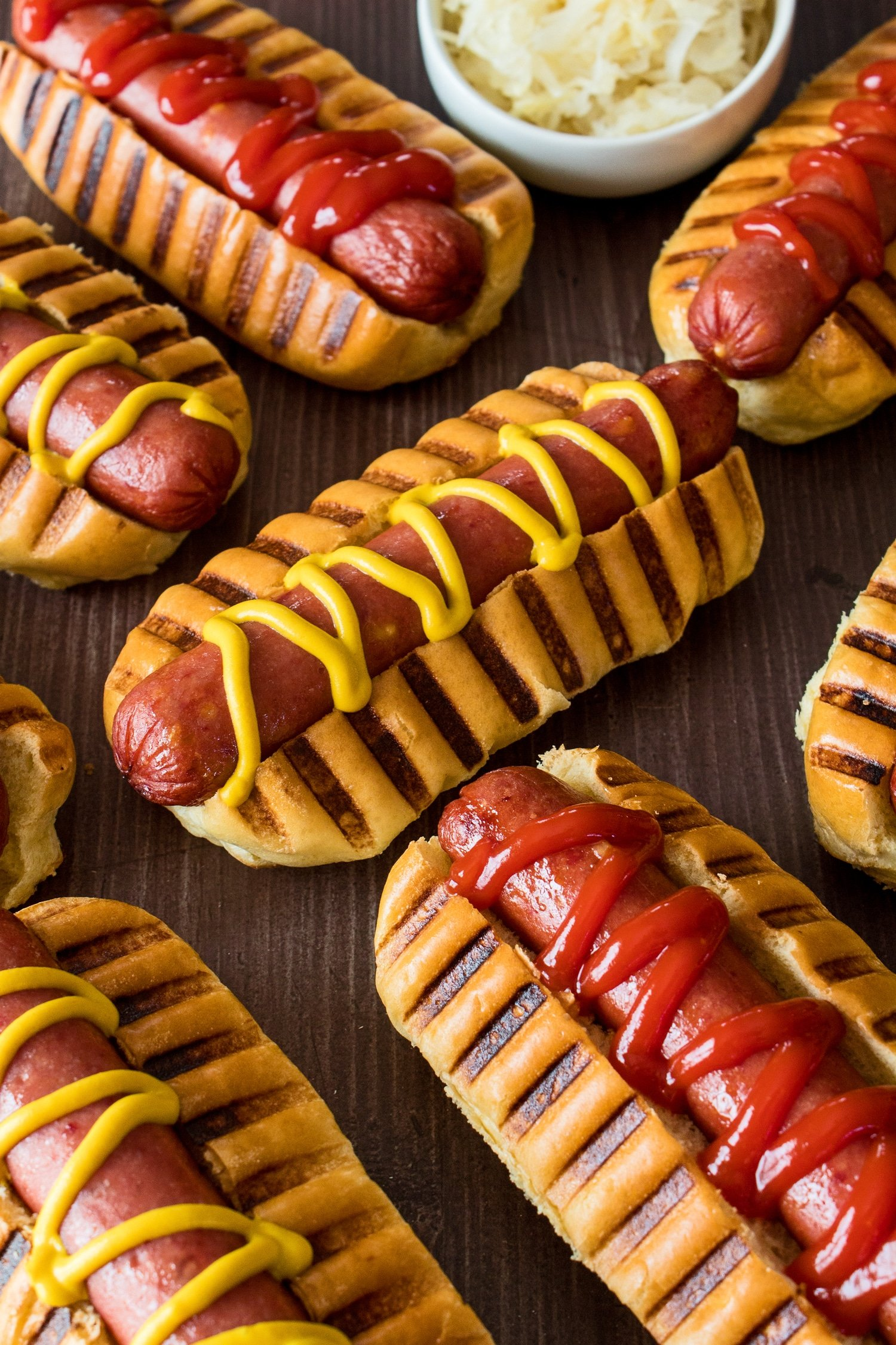 Vertical image taken from the side with the ketchup and mustard garnished air fryer hot dogs in the front and sauerkraut in the background.