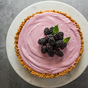 easy almost no bake blackberry cream pie shown overhead on a marble round stand with grey background and fresh blackberries added to the center top of the pie before serving garnished with a few single mint leaves