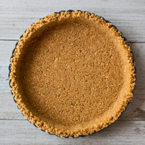 square overhead image of a completed homemade graham cracker crust in a metal fluted round tart pan on a light wooden background