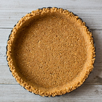 Imagen aérea cuadrada de una corteza de galleta Graham casera completada en un molde para tarta redondo acanalado de metal sobre un fondo de madera clara