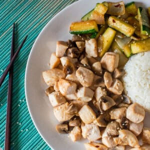 hibachi chicken served with hibachi zucchini and rice on a white plate with light ombre aqua background