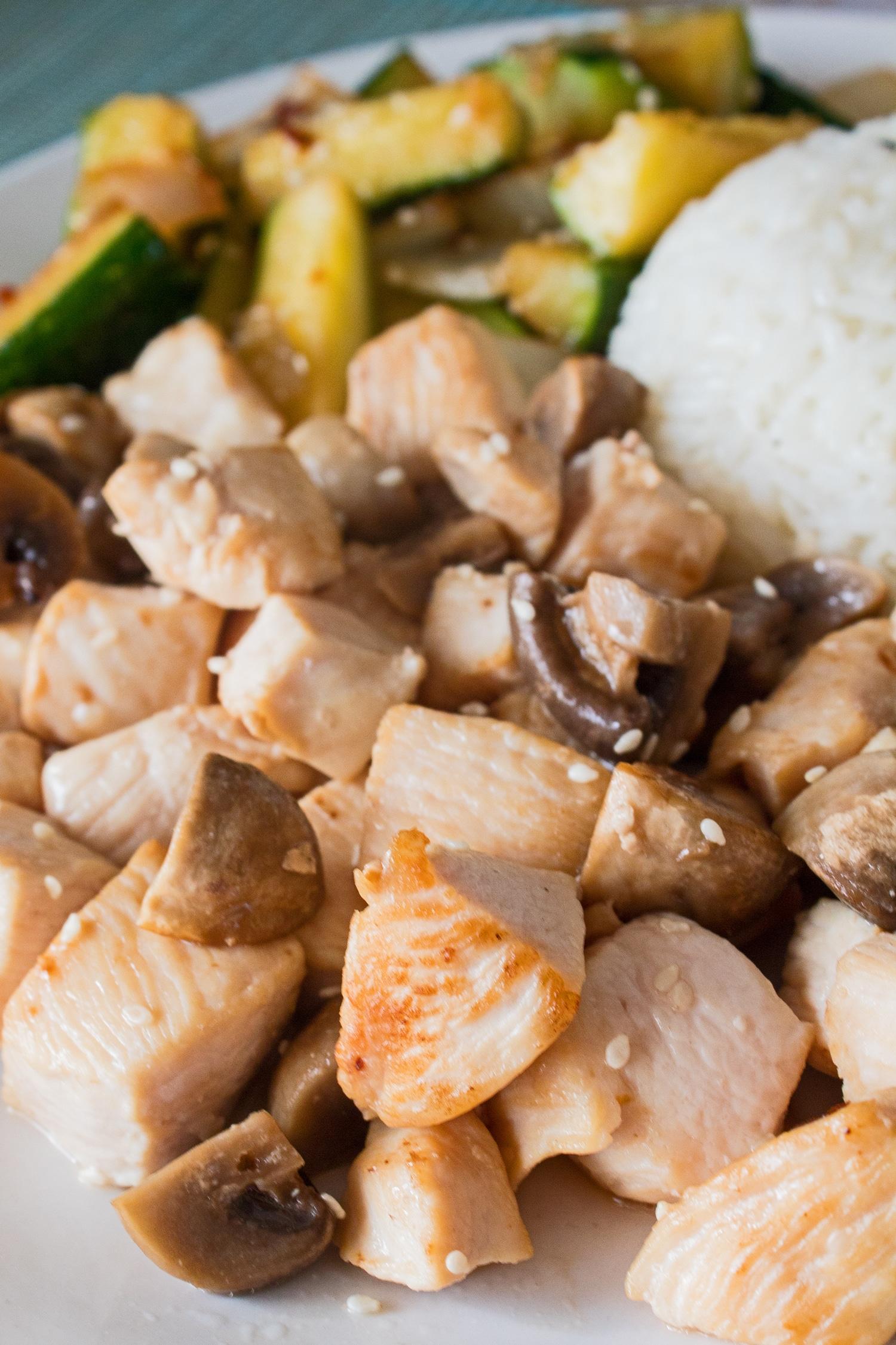 Acercamiento de pollo hibachi con champiñones en una placa blanca con calabacín hibachi y arroz en el fondo
