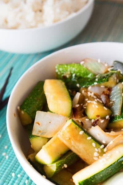 طبق ستيك هاوس ياباني كوسة هيباتشي والبصل في وعاء أبيض مع وعاء آخر من الأرز الأبيض في الخلفية