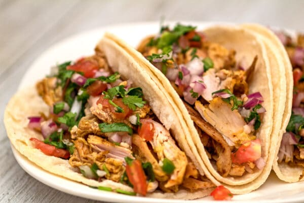 horizontal image showing a close up view of the turkey carnitas garnished and served with fresh homemade pico de gallo served on white corn tortillas on a white plate with light wood grain background