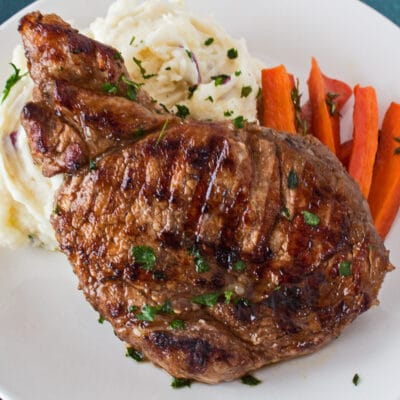 single marinated grilled pork chop shown on a white plate with mashed potatoes and sliced carrots