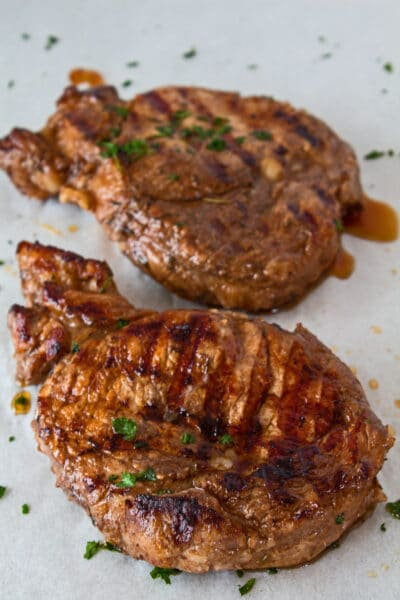 two marinated grilled pork chops shown on parchment paper while resting