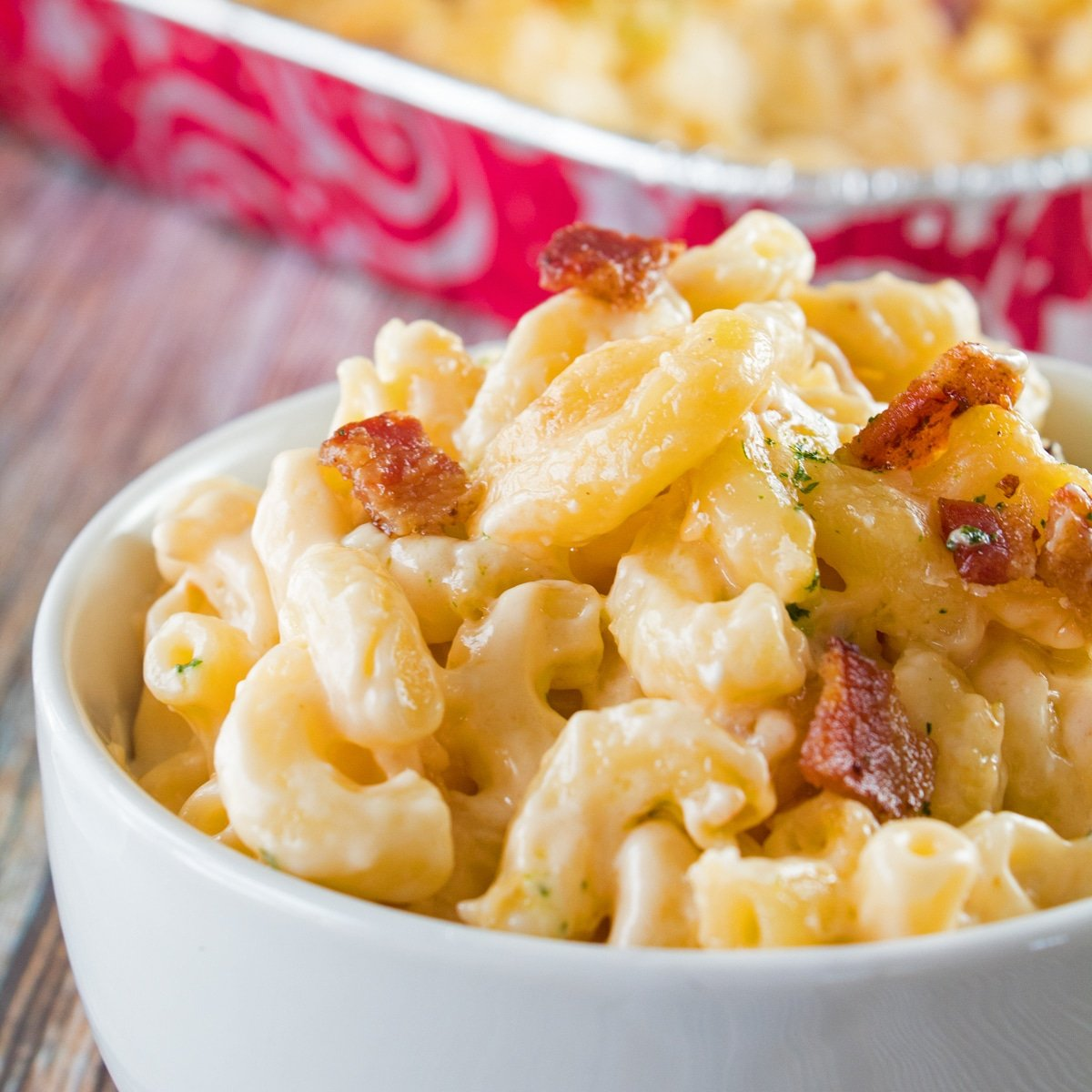 Portioned serving of smoked mac and cheese in a white bowl with the aluminum baking tray in the background.