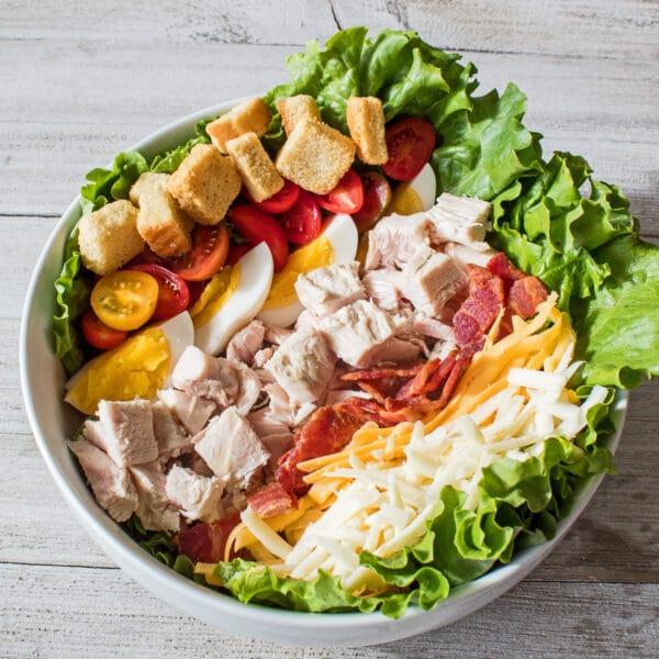 Imagen aérea de la ensalada del chef en un gran tazón de servir blanco sobre un fondo de madera gris como la imagen destacada más grande