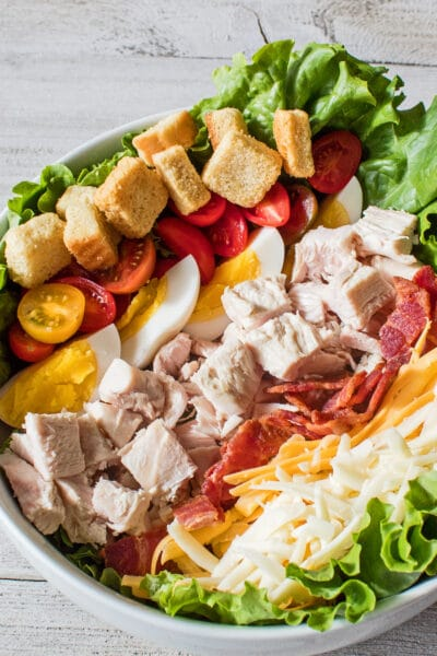 close up vertical image showing the layered turkey meat bacon cheeses had boiled eggs tomatoes and croutons on a bed of leaf lettuce