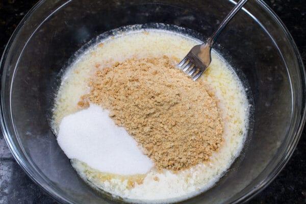 migas de galletas Graham trituradas con azúcar y mantequilla derretida listas para combinar con un tenedor