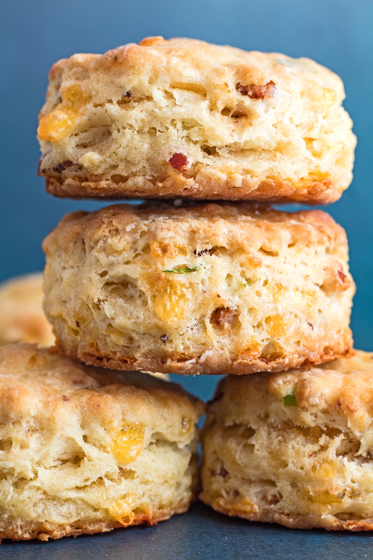 tall image of stacked tasty cheddar bacon chive biscuits freshly baked and ready to enjoy