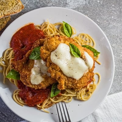 small square photo showing an overhead view of the chicken parmesan served over a bed of thin spaghetti pasta with marinara sauce and two Panko and Parmesan crusted chicken breast cutlets with melted mozzarella on the center of each cut garnished with a few fresh leaves of baby Genovese basil
