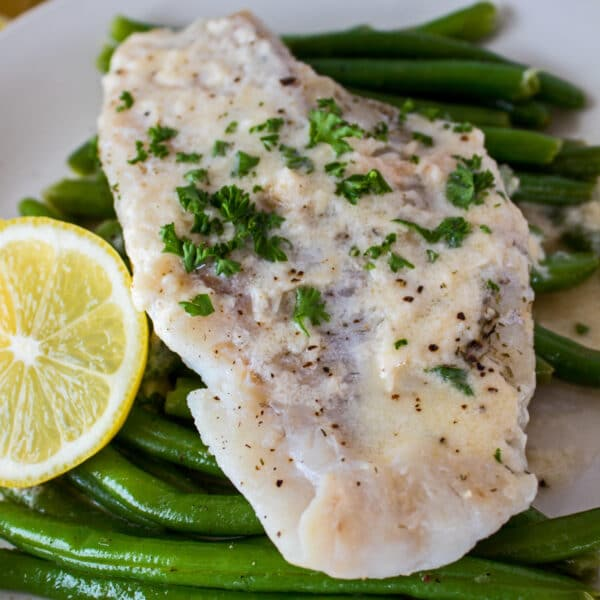 large square angled overhead image of foil packet grilled haddock served on a bed of green beans with lemon on the side