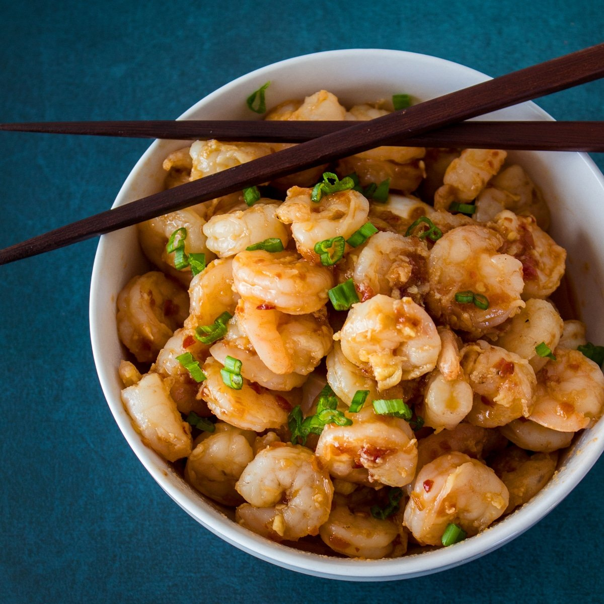 Large square overhead image of hunan shrimp served in a white bowl with chopsticks placed on rim set on a dark blue background.