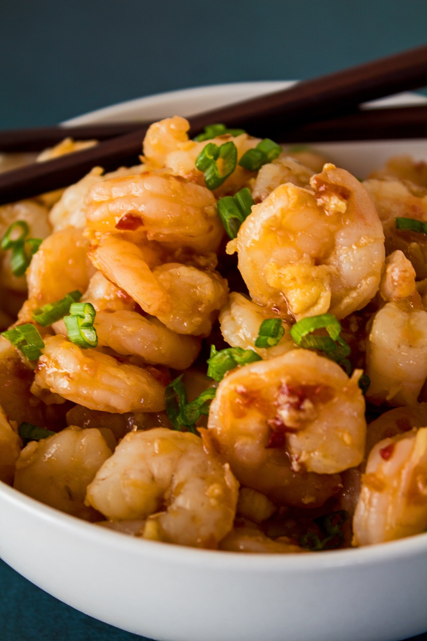 tall vertical image a closeup side view of the served hunan shrimp garnished with chopped green onions served in a white bowl on blue background