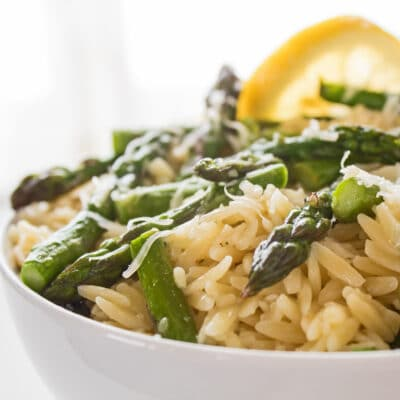 large square photo being a closeup sideview of the dished lemon asparagus orzo pasta