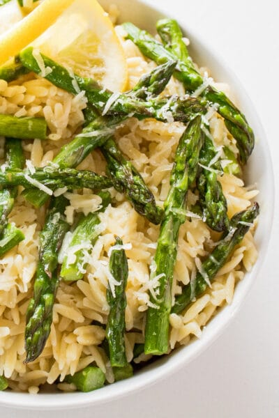 vertical overhead image of orzo pasta with asparagus and lemon sauce garnished with grated parmesan and a lemon twist in a white bowl and background