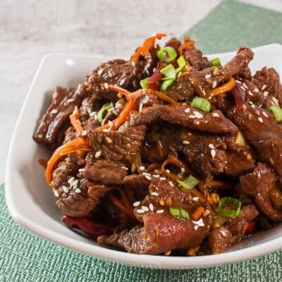 large square image showing cooked mongolian beef from a slightly overhead side view in a white bowl on light background