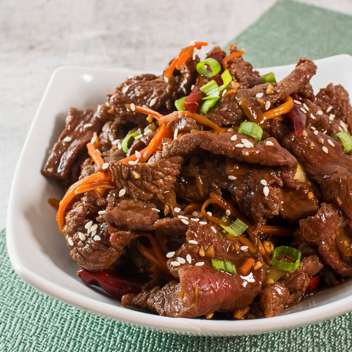 Large square image showing cooked mongolian beef from a slightly overhead side view in a white bowl on light background.
