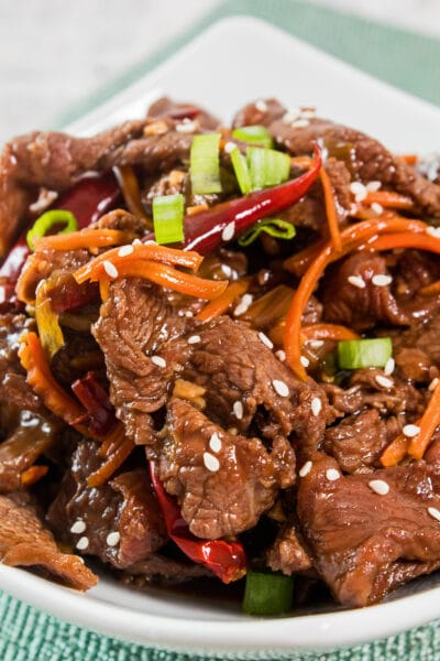 closeup vertical image of dished up mongolian beef garnished with sliced green onions and sesame seeds