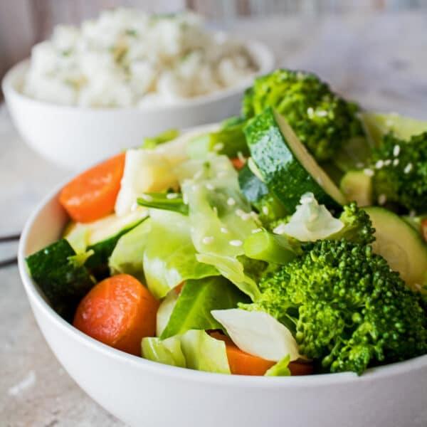 stort firkantet billede taget fra en sidebillede af panda-ekspressblandede grøntsager serveret i en hvid skål på en lys baggrund med en skål ris i baggrunden