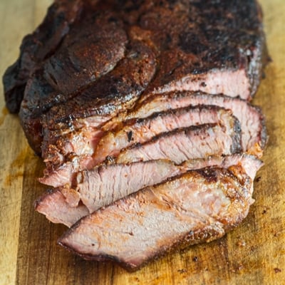 a small square image showing tender juicy sliced smoked beef chuck roast after smoking on the cutting board