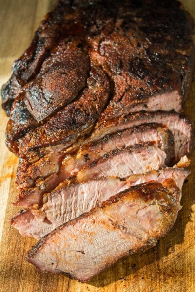 a large vertical image slightly overhead image showing tender juicy sliced smoked beef chuck roast after smoking on the cutting board