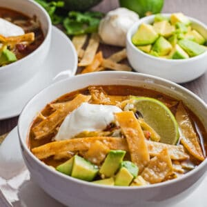 large square perfect chicken tortilla soup with garnish served in white bowls.