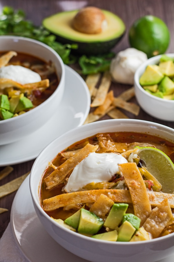 vertical image of two bowls of chicken tortilla soup.