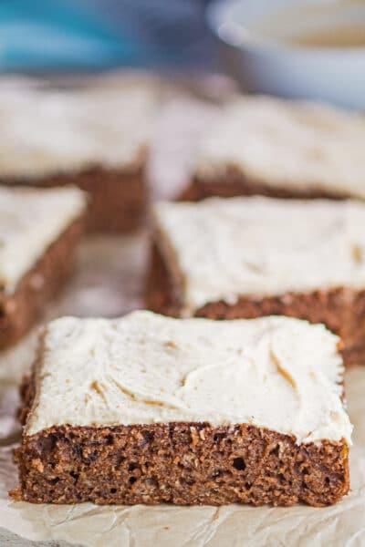 Imagen alta de tarta de plátano chocolate en rodajas con tazón de glaseado en segundo plano.