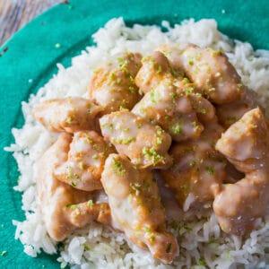 ángulo de arriba cuadrado grande del pollo servido con arroz en un plato verde.