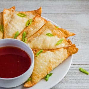 large square angled overhead image of the plated cream cheese wontons with sweet and sour sauce for dipping.