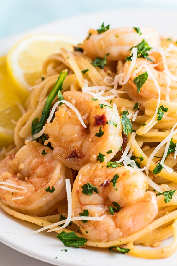 tall closeup of the garlic shrimp pasta served on white dish with lemon wedges.