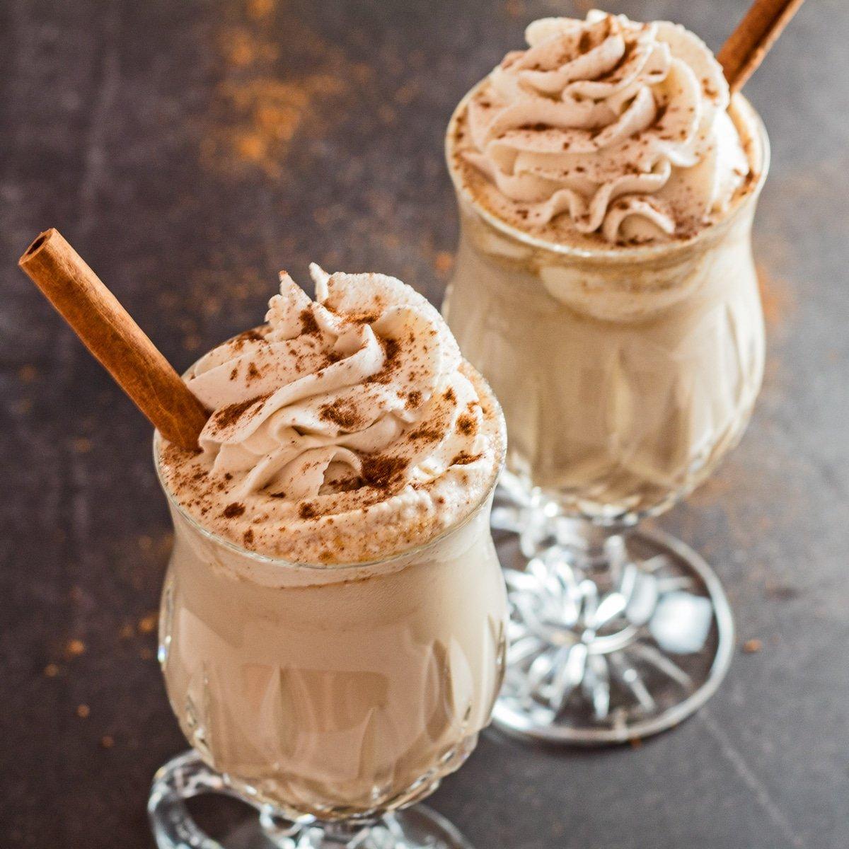 Gran sobrecarga en ángulo de café con leche helado de especias de calabaza cubierto con crema batida.