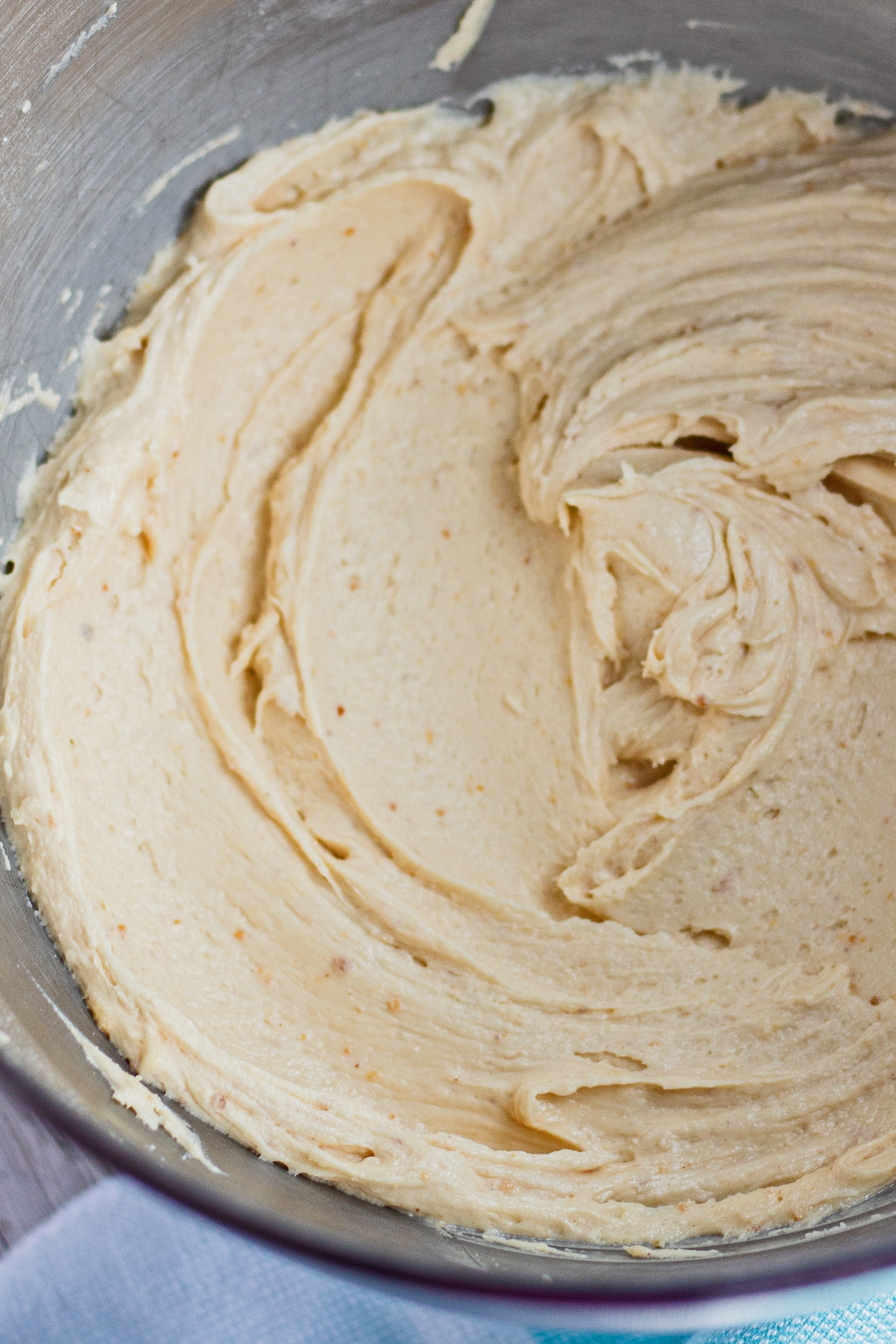 closeup vertical overhead of peanut butter cream cheese frosting in the stand mixer bowl