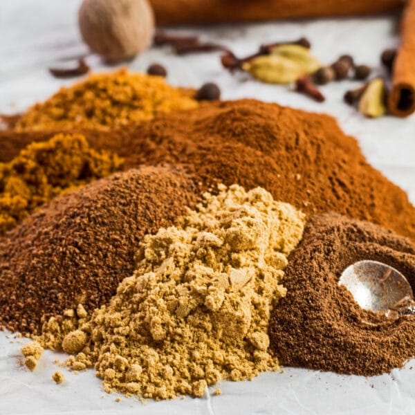 Large square image of the ground spices poured onto a white background with whole spices for the pumpkin pie spice in background.