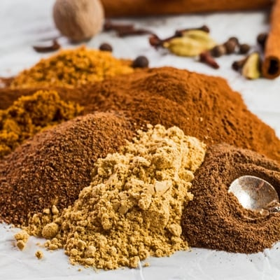small square image of the ground spices poured onto a white background with whole spices for the pumpkin pie spice in background.