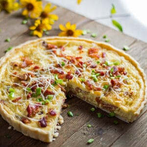 large square image baked quiche lorraine sliced and being served