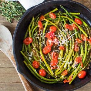 grande imagem quadrada espargos refogados e tomate cereja em frigideira de ferro fundido.