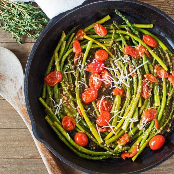 stort kvadratisk billede sauteret asparges og cherrytomater i stegepande.