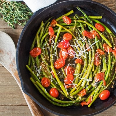 sauteed asparagus and cherry tomatoes in cast iron skillet.
