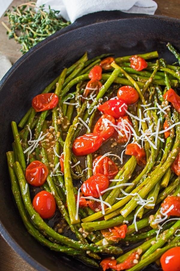 gambar tinggi asparagus dan tomato dalam wajan besi tuang.
