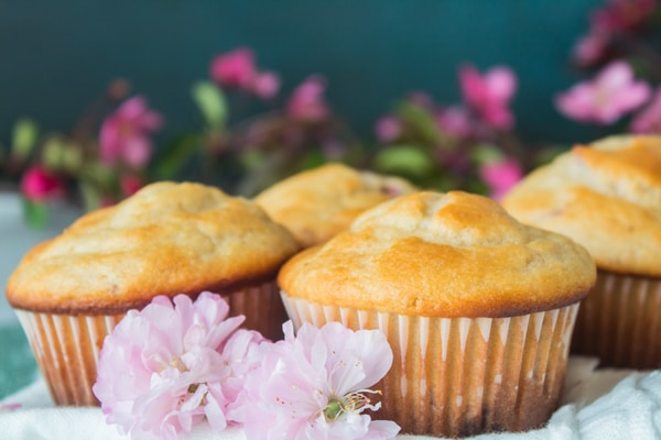 Lauren's wide photo of several of the strawberry muffins placed together with flowers around them.